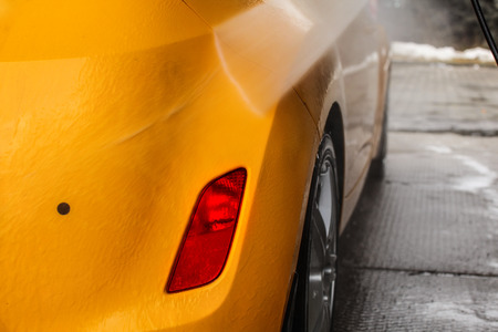 Detail on dark yellow car back being washed with jet water stream in carwash.