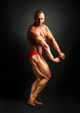 Studio shot of male bodybuilder posing, showing front and side muscles with black background.