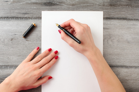 View from above to woman's hands with red nails, holding black fountain ink pen with gold nib, ready to write something on empty piece of paper laying on gray wood table. Banque d'images