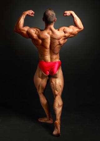 Uomo giovane bodybuilder che flette indietro la doppia posa bicpes, mostrando il suo enorme trapezio, romboide, elevatore, latissimus dorsi e muscoli delle gambe. Studio girato su sfondo nero.