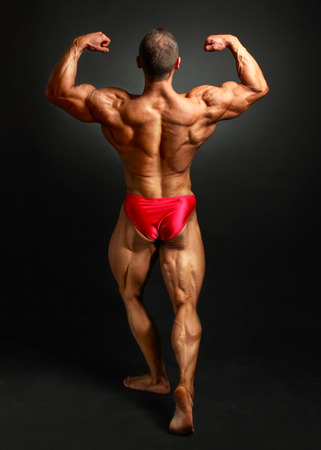 Young bodybuilder man flexing back double bicpes pose, showing his huge trapezius, rhomboid, levator, latissimus dorsi and legs muscles. Studio shot on black background.