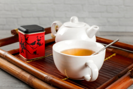 Cup of hot black tea with teapot and metal tea dose in background,  served on bamboo wood tray.