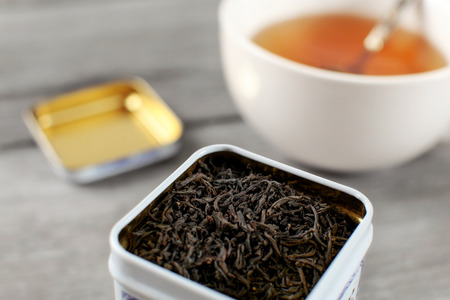 Black loose tea in metal tin, with blurred cup of hot amber drink in background.