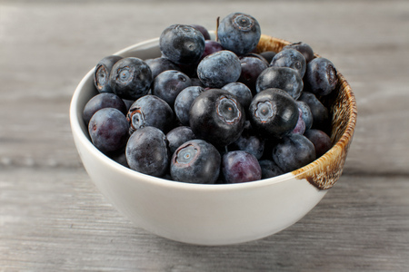 Close up on small white porcelain bowl full of blueberries.