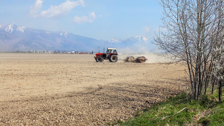 Tractor pulling heavy metal roller over dry field, with mountains, little bit snow on top, in background. Spring field preparation. Stok Fotoğraf