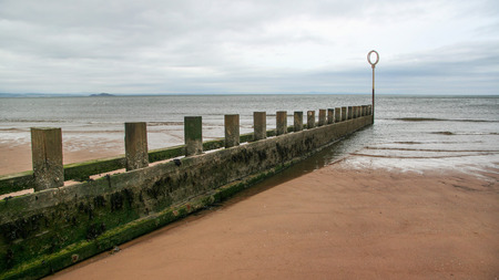 Old wooden and stone groyne structure covered with green algae on Portobello beach, low tide North sea in the backgroud, on overcast day. Edinburgh, Scotland. Standard-Bild - 114271548