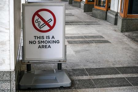 Dies ist ein Rauchverbotsschild auf einer noblen Straße, einem Marmorboden und den unteren Wänden von Geschäften