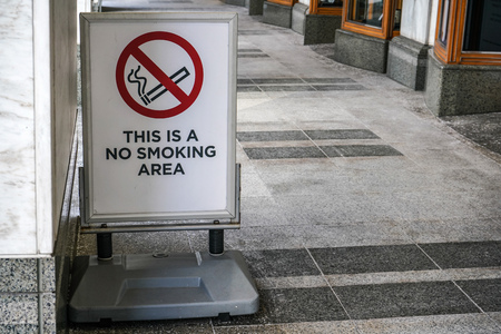 This is a no smoking area sign on posh looking street, marble pavement, and bottom walls of shops