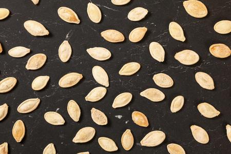 White roasted, salted pumpkin seeds on black marble like working board, overhead shot