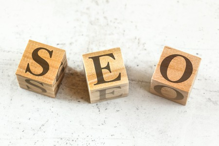 Three wooden cubes with letters SEO stands for Search Engine Optimization on white board. 스톡 콘텐츠