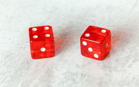 Two translucent red craps dices on white board showing Easy Six Jimmie Hicks umber 4 and 2