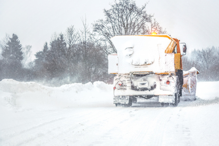 Snow plow gritter cleaning road during heavy winter snow storm