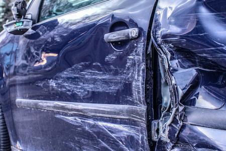 Detail of car after accident, side metal plates deformed after crash hit.