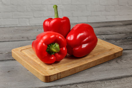 Three whole red bell peppers on chopping board 写真素材