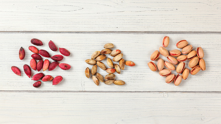 Red Turkish pistachios on white boards. Partly dried fruits, when peeled, nuts are inside, and finally, roasted pistachio. Tabletop view.