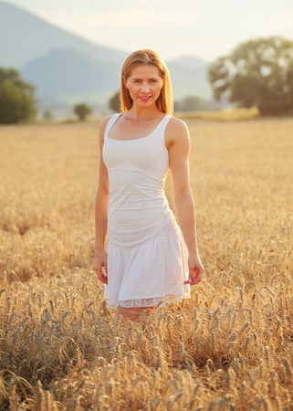 Young slim woman in white dress standing in wheat field in sunset haze backlight.