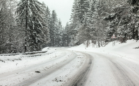 Curve on forest road covered with snow, more falling, dangerous driving conditions. Stock fotó