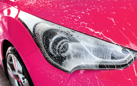 Pink car front light washed in self serve carwash, white shampoo foam flowing on glass.