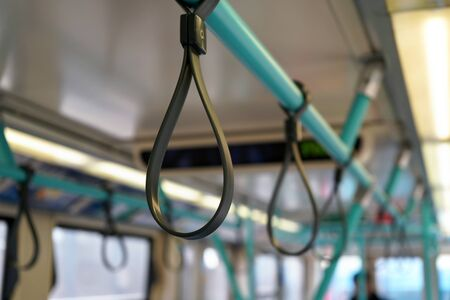 Rubber handle loops on light blue tube, for passengers to hold safely during bus train journey Reklamní fotografie