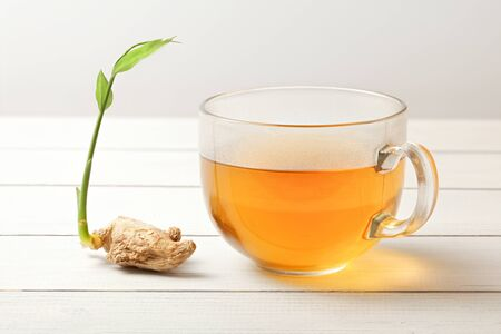 Cup of ginger tea (hot steam and moisture drops on glass), dry root with green spring next to it.