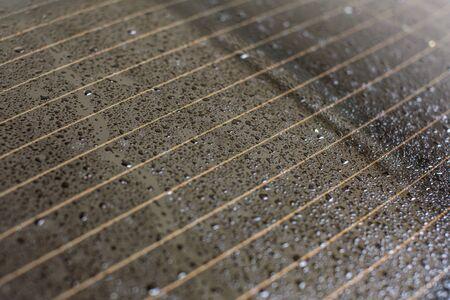 Drops of water on rear car window, orange heating stripes in glass.