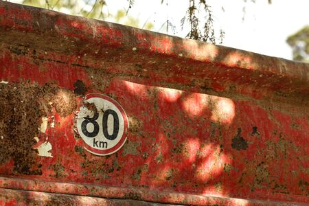 Detail on speed limit 80 km/h sign at the rear of old dump truck cargo container.