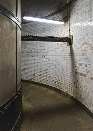 Interno del tunnel pedonale di Greenwich, pareti sporche di grunge e pavimento in uno stretto corridoio illuminato da luce al neon