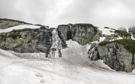 Waterfall Skok in High Tatras, Slovakia, during overcast spring day, dirty snow still covering most of ground