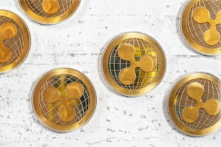 XRP ripple cryptocurrency golden coins on white stone like board, flat lay view from above