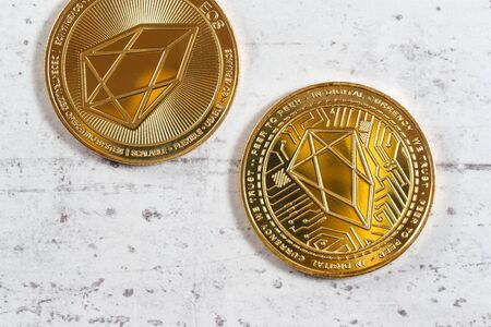 Top down view, detail of golden commemorative EOS - EOSIO cryptocurrency - coins on white stone board