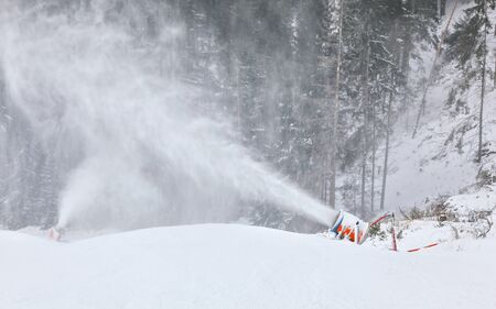 Orange and blue snow making cannon spreading ice crystals over ski piste, trees in background