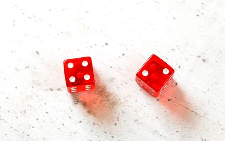 Two red craps dices showing Easy Six Jimmie Hicks number 4 and 2 overhead shot on white board