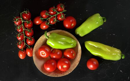 Tomatoes and green bell peppers in small bowl and on black board, view from above