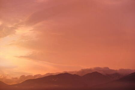 Orange and pink sky after sunset, silhouettes of mountains below - can be used as background with subjects placed in front