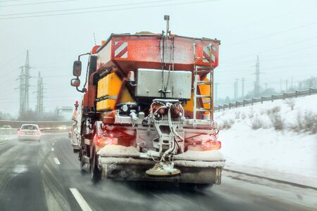 Bright orange gritter maintenance truck spreading deicing salt and sand on highway, view from car driving behind