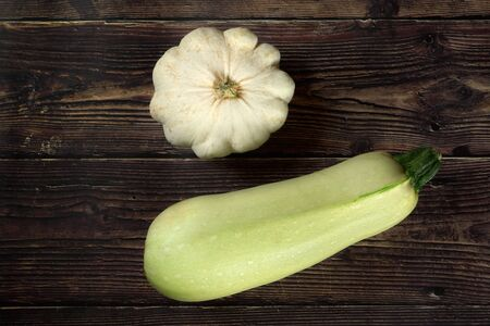 Pattypan squash and light green courgette on dark wooden board, view from above