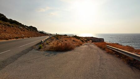Afternoon sun shines on asphalt road leading down to beach, sea in distance - typical landscape in Karpas region of Northern Cyprus Banco de Imagens