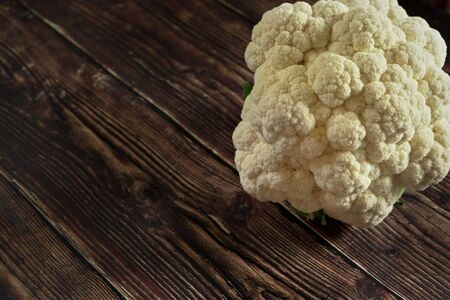 White cauliflower head with no leaves on dark wooden board, space for text left down
