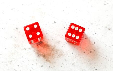 Two red craps dices showing Easy Ten number four and six overhead shot on white board