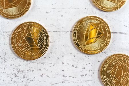 Top down view, golden commemorative EOS - EOSIO cryptocurrency - coins scattered on white stone board Imagens