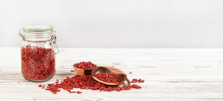 Dried goji aka. wolfberry inside glass bottle, some in wooden bowls and spilled on white boards desk, space for text on right side