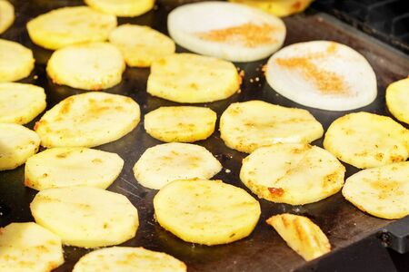 Potatoes cut to thin slices grilled on electric grill Banco de Imagens