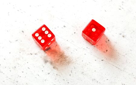 Two red craps dices showing Natural or Seven Out number 6 and 1 overhead shot on white board.