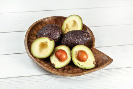 Ripe dark brown avocados - Hass Bilse variety - some cut in half, seeds visible, in wooden carved bowl on white boards desk. Banco de Imagens