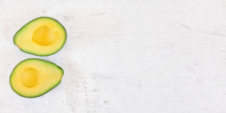 Two avocado halves with bright yellow pulp on white stone desk, view from above - wide banner space for text on right side.
