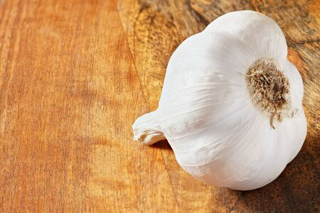 Single garlic bulb on wooden kitchen board, space for text left side, closeup macro.