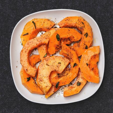 Grilled butternut squash, bright orange pieces with small basil leaves on square white plate, view from above.