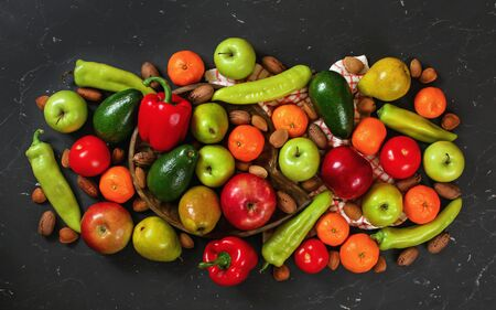Mixed vegetables and fruit on black marble like board, view from above.