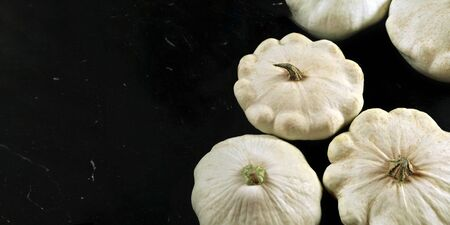 Group of white pattypan squash on black board, space for text left side.