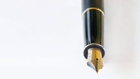 Golden coloured fountain pen nib detailed macro closeup - all imperfections and corrosion visible on metal.